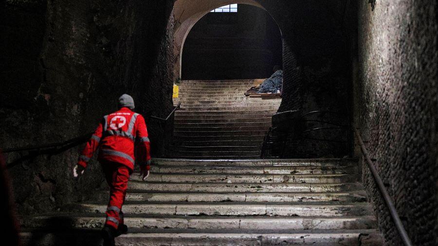 Un trabajador de la Cruz Roja revisa a un indigente durmiendo en una escalinata cerca del Coliseo en Roma, Italia, el 17 de marzo de 2020 (REUTERS/Guglielmo Mangiapane)